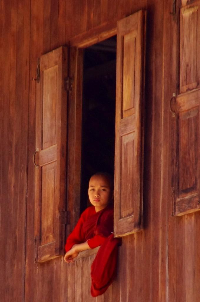 Ein junger Mönch schaut aus dem Fenster des Teak-Klosters nördlich von Hsipaw, in welchem sich ein bekannter Bambus-Buddha befindet.