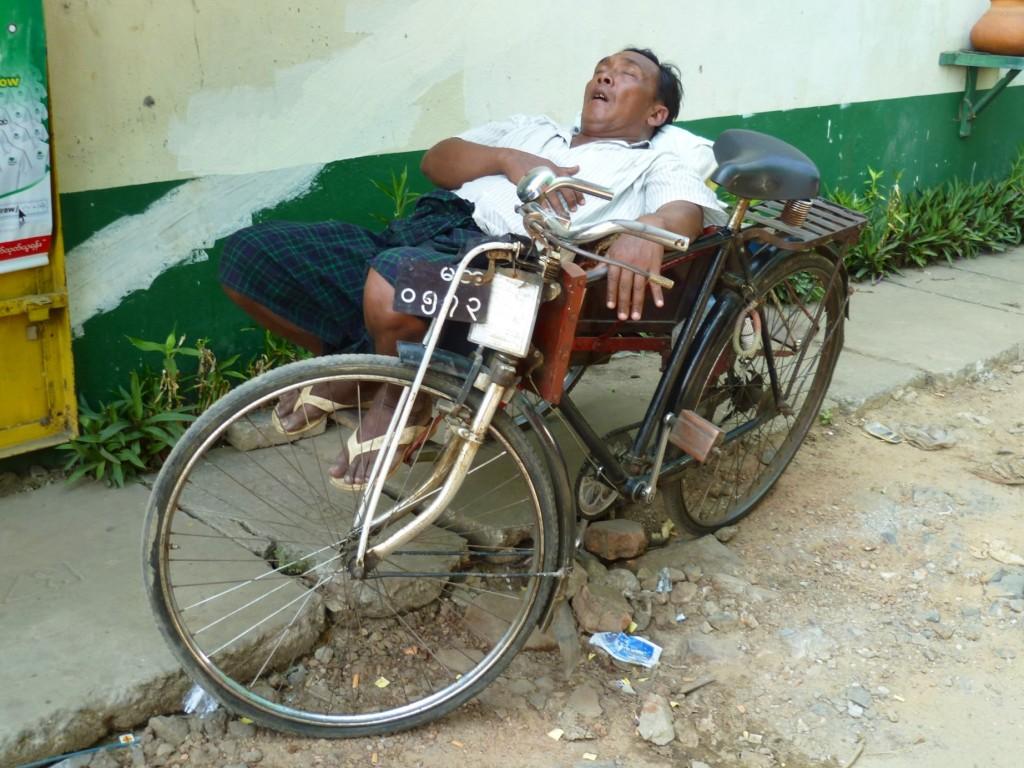 Yangon: Bei der Hitze wird jede freie Minute genutzt, um sich zum Ausruhen in den Schatten zu begeben. Gerade der Job eines Trishaw-Fahrers ist mehr als anstrengend.