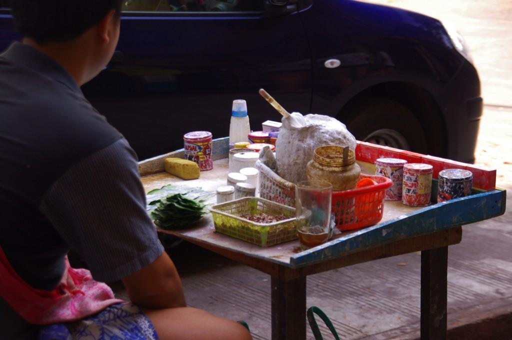 Yangon: In ganz Myanmar kauen die Menschen Betelnuss, wovon sie rote bis schwarz-rote Zähne und ein ebensolches Zahnfleisch bekommen. Um den bittereren Geschmack und die zum Teil giftigen Inhaltsstoffe einigermaßen erträglich zu machen, werden kleine Kau-Säckchen aus Blättern gebunden, in die eine Ladung Kalk und weitere Ingredienzien wie Anis hinein kommen. Einige dieser Stände haben 24 Stunden geöffnet, damit man immer etwas zum Kauen hat.