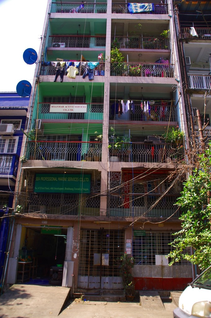 Yangon: Jeder Bewohner eines Hauses hat seine eigene Leine mit einer Klammer vom Balkon herunter runterhängen. Post, Mitteilungen, aber auch die Einkäufe werden so in die Wohnungen herauf gezogen.